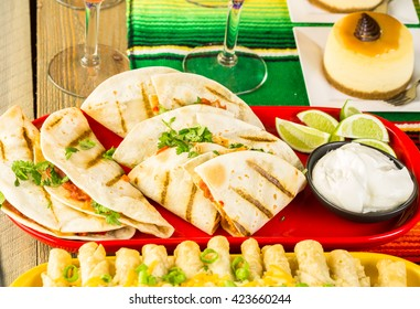 Fiesta party buffet table with chicken quesadilla and other traditional Mexican food.