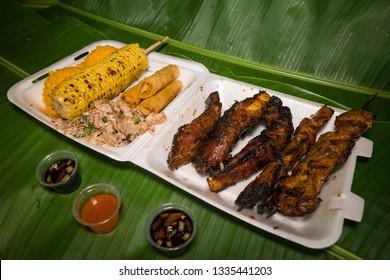 Fiesta plate with Chamorro finadene sauce. Guam local food. Banana leaves background. Bbq ribs, bbq-chicken, kelaguen, red-rice, corn on the cob, fried-lumpia.