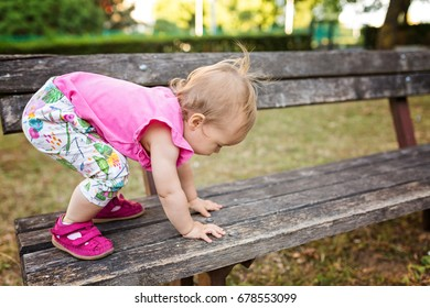 Fifteen months old baby girl climbing up the wooden bench in the park