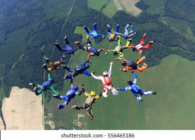 Fifteen skydivers have made a figure. The leader of group is in white suit. He's making a signal to change position.