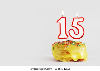 Fifteen  years anniversary. Birthday cupcake with white burning candles with red border in the form of number Fifteen. Light gray background with copy space