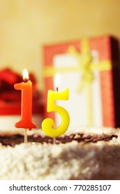 Fifteen years. Birthday cake with burning candles and gifts