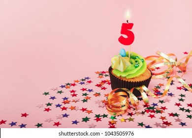 Fifth 5th birthday cupcake with candle and sprinkles on pink background. Card mockup, copy space. Birthday, party, holiday concept