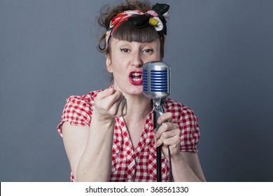 fifties singer in studio - talking 30s female rocker and vocal artist with retro style performing in old fashioned microphone, gray background
