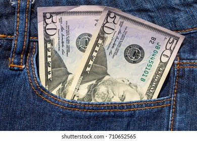 Fifty American dollars bills in the pocket of blue jeans
