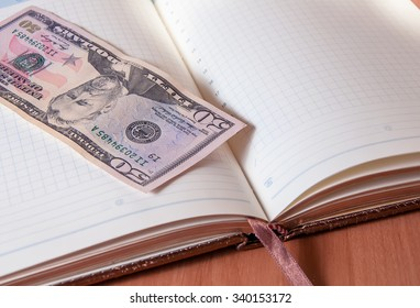 Fifty American dollars and Notepad on wooden table. Fifty American dollars and Notepad