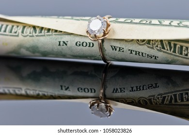 fifty dollar bill is rolled into a tube and inserted into an elegant women's gold ring