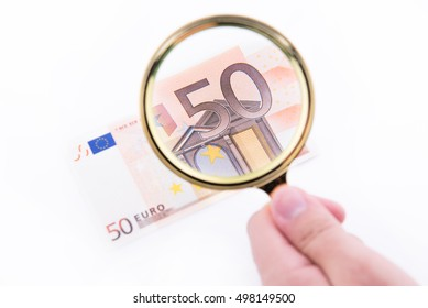 Fifty euro banknote with magnifying glass over white background