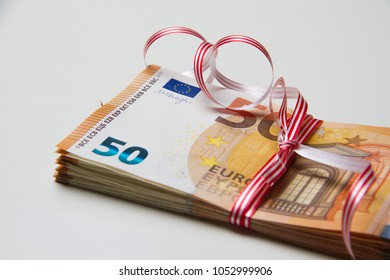 Fifty euros banknote with red ribbon as gift of money on white background