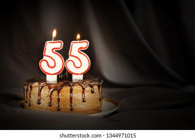 Fifty five years anniversary. Birthday chocolate cake with white burning candles in the form of number Fifty five. Dark background with black cloth