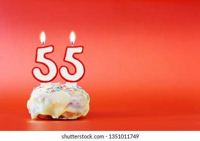 Fifty five years birthday. Cupcake with white burning candle in the form of number 55. Vivid red background with copy space