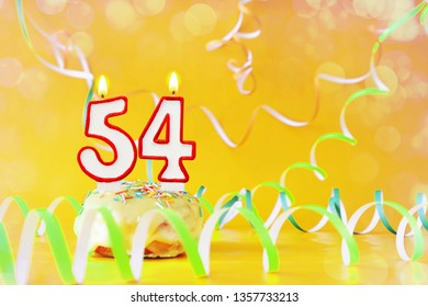 Fifty four years birthday. Cupcake with burning candles in the form of number 54. Bright yellow background with copy space