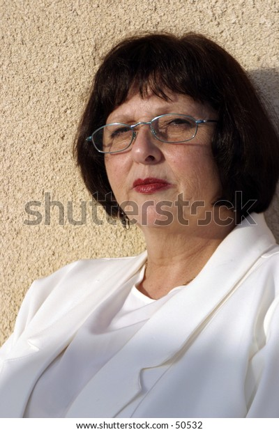 A fifty something woman looking through blue framed glasses.