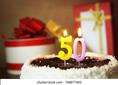 Fifty years birthday. Cake with burning candles and gifts