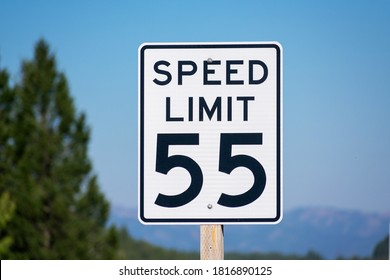 Fifty-five mph speed limit sign on highway. Speed zone traffic sign against blurred tree landscape and blue sky.