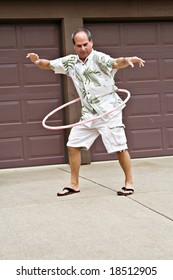 Fifty-five year old man plays with a hula hoop.