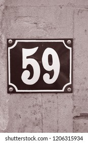 Fifty-Nine Number Sign on Stone Wall in Black and White Sepia Tone