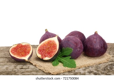 fig fruits with leaves on old wooden table with white background