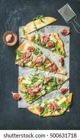 Fig, prosciutto, arugula and sage flatbread pizza cut into pieces with glass of rose wine over black grunge stone background, top view, vertical composition