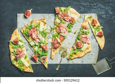 Fig, prosciutto, arugula and sage flatbread pizza cut into pieces over black grunge stone background, top view, horizontal composition