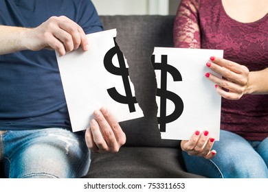 Fight about money or financial argument concept. Man and woman holding ripped paper with dollar sign.