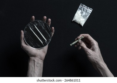 The fight against drugs and drug addiction topic: addict hand holds a mirror with strips of cocaine and drugs around her lie on a dark background, top view in the studio