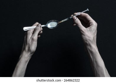 The fight against drugs and drug addiction topic: hand holding a syringe and a drug addict gains from a spoon liquid drug on a dark background