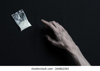 The fight against drugs and drug addiction topic: addict hand reaches for the package of cocaine on a dark background in the studio top view