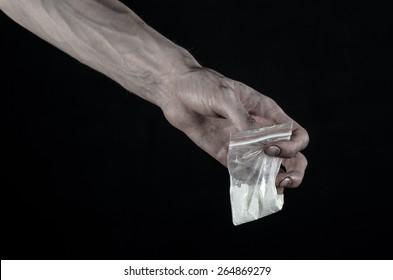 The fight against drugs and drug addiction topic: dirty hand holding a bag addict cocaine on a black background in the studio
