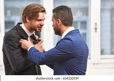 fight, business conflict, aggressive young men in formal wear or businessmen fight with tie near office window, boss and employee