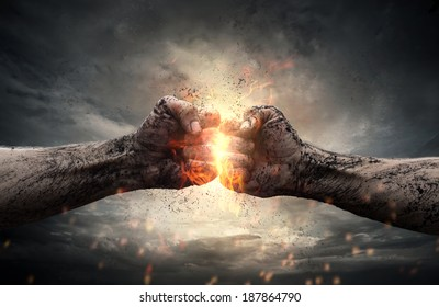Fight, close up of two fists hitting each other over dark, dramatic sky