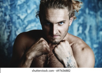 Fight club, MMA. Portrait of a muscular man fighter standing with clenched fists.