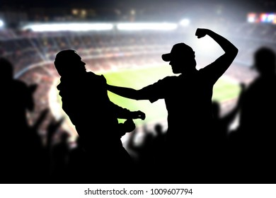 Fight in a football game crowd. Angry man hitting another spectator in soccer match audience. Violent argument between two fans of different teams and clubs. Hooligans and violence in sport event.