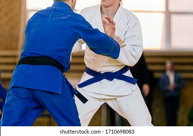 fight judo wrestlers in white and blue kimono