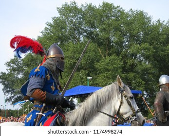 Fight with swords in a jousting tournament. Knight in armor riding a horse. A medieval battle.
