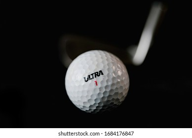 The Fight with virus. Allegory. Golf ball and golf club on black background. ( ULTRA word is not a brand, it is kind (type) of balls.)