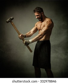 fighter with hammer on hands, dark and foggy background