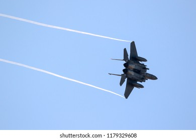 Fighter jet with contrails on a blue sky