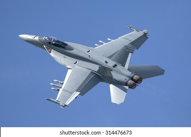 Fighter jet loaded with missiles flying against a blue sky