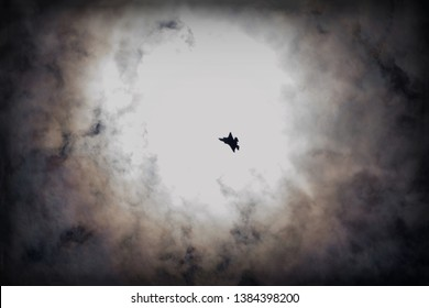 Fighter jet in the sky against the sun