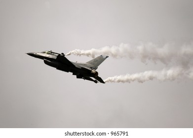 Fighter jet with vapor trails against a brooding steel sky