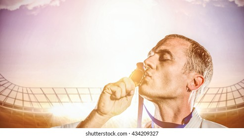 Fighter kissing his gold medal against race track