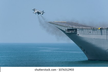 A fighter plane during a vertical take-off from an aircraft carrier at sea. A spanish navy combat plane during a war operation at sea