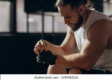 Fighter puts on hand wraps while sitting on the edge of a boxing ring in a musty boxing gym, camera rotates around from side to front