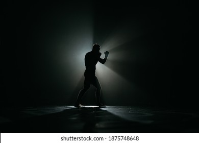 Fighter striking a blow. Professional sport. Fighting. Strength. Fighter in a moody light and grain mood.  				boxer training with punching bag in dark sports hall