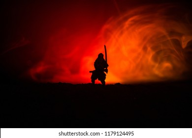 Fighter with a sword silhouette a sky ninja. Samurai on top of mountain with dark toned foggy background. Selective focus