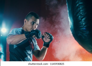 Fighter training to hit a punching bag in the gym. Portrait of the young man boxing fighter Practicing. Guy is an athlete doing workout.
