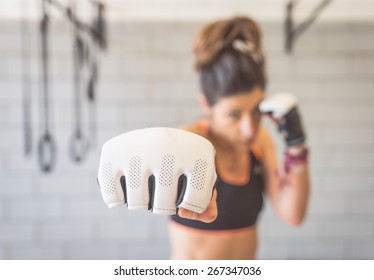 fighter woman fist close up. straight focus on the glove with the rest of the image on blur. concept about sport and people