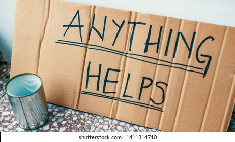 "Fighting adversity. Homeless man with sign and money tin. Help, please. Poverty. ""Anything helps"" says beggar's cardboard sign."
