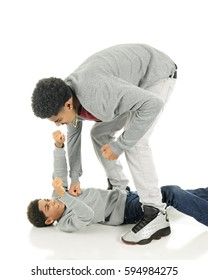 Fighting brothers.  A tall older teen punching his elementary brother who is flat on his back but punching back.  On a white background.